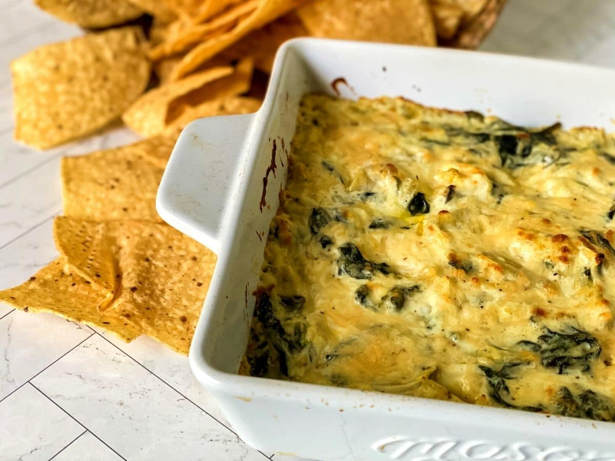 Side of white baking dish with spinach aritchoke dip on white tile