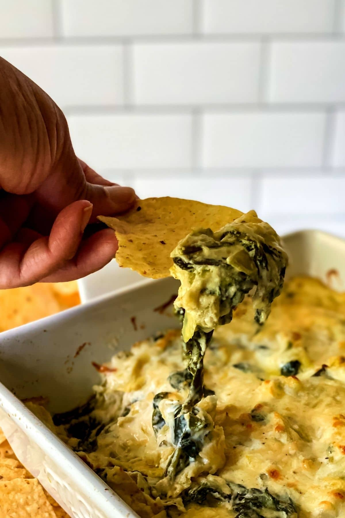 Hand holding chip with spinach dip