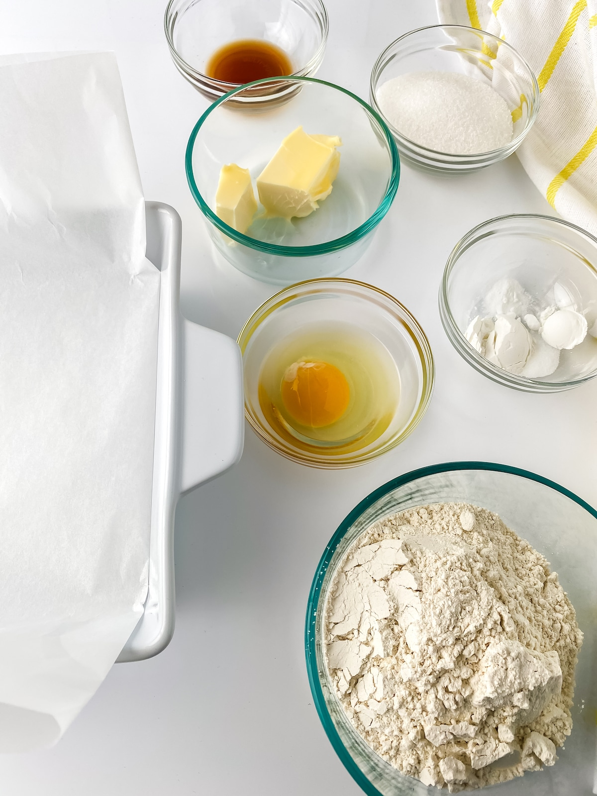 Ingredients for sugar cookie bars in glass bowls on white table
