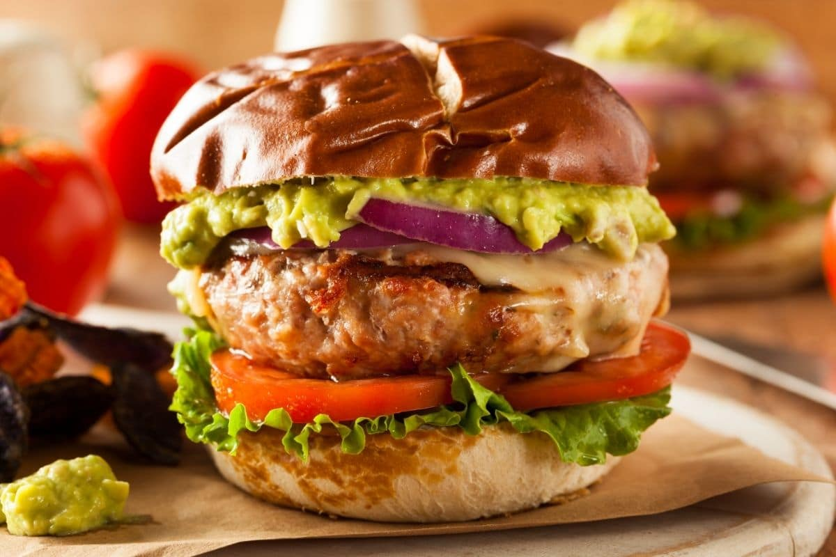 Turkey burger with tomato lettuce red onion sauce and gaucamole on soft bun on paper