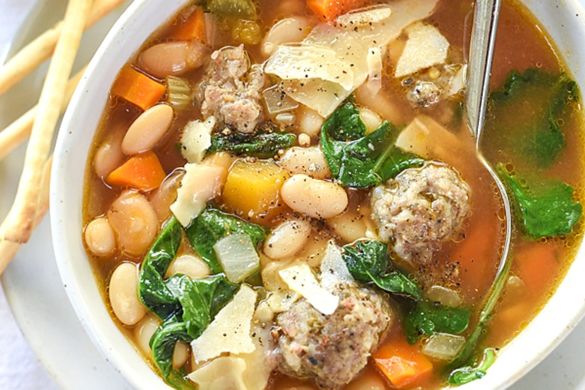 Tuscan White Bean and Sausage Soup on a white bowl, close up