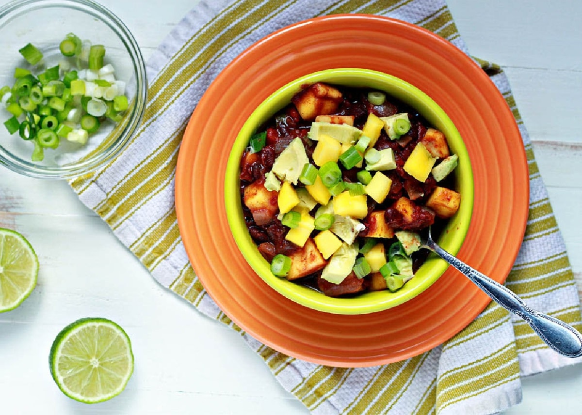 Black Bean and Mango Chili topped with avocado slices, spring onions and mango
