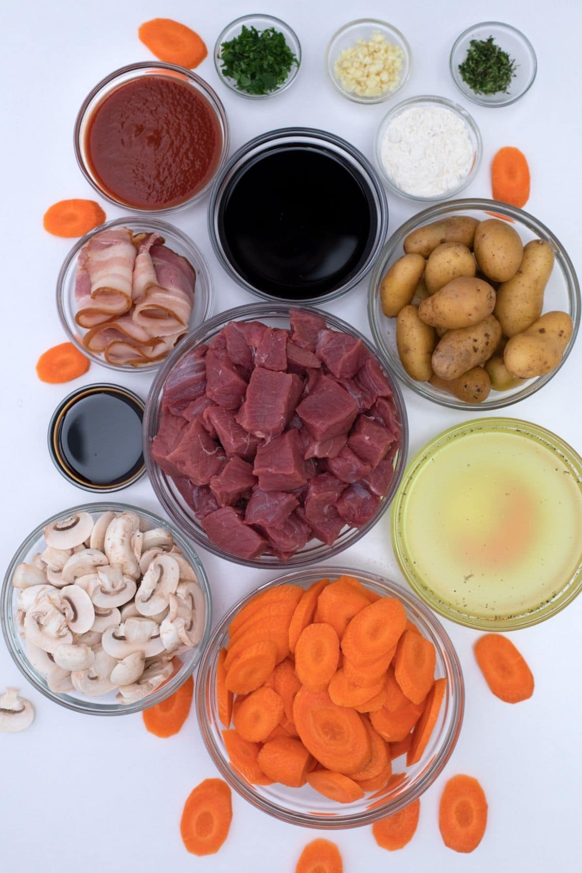 Ingredients for beef bourguignon in glass bowls on white table
