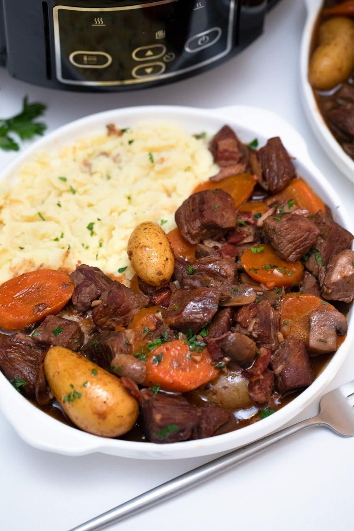 Round white bowl of beef bourguignon and potatoes on white table