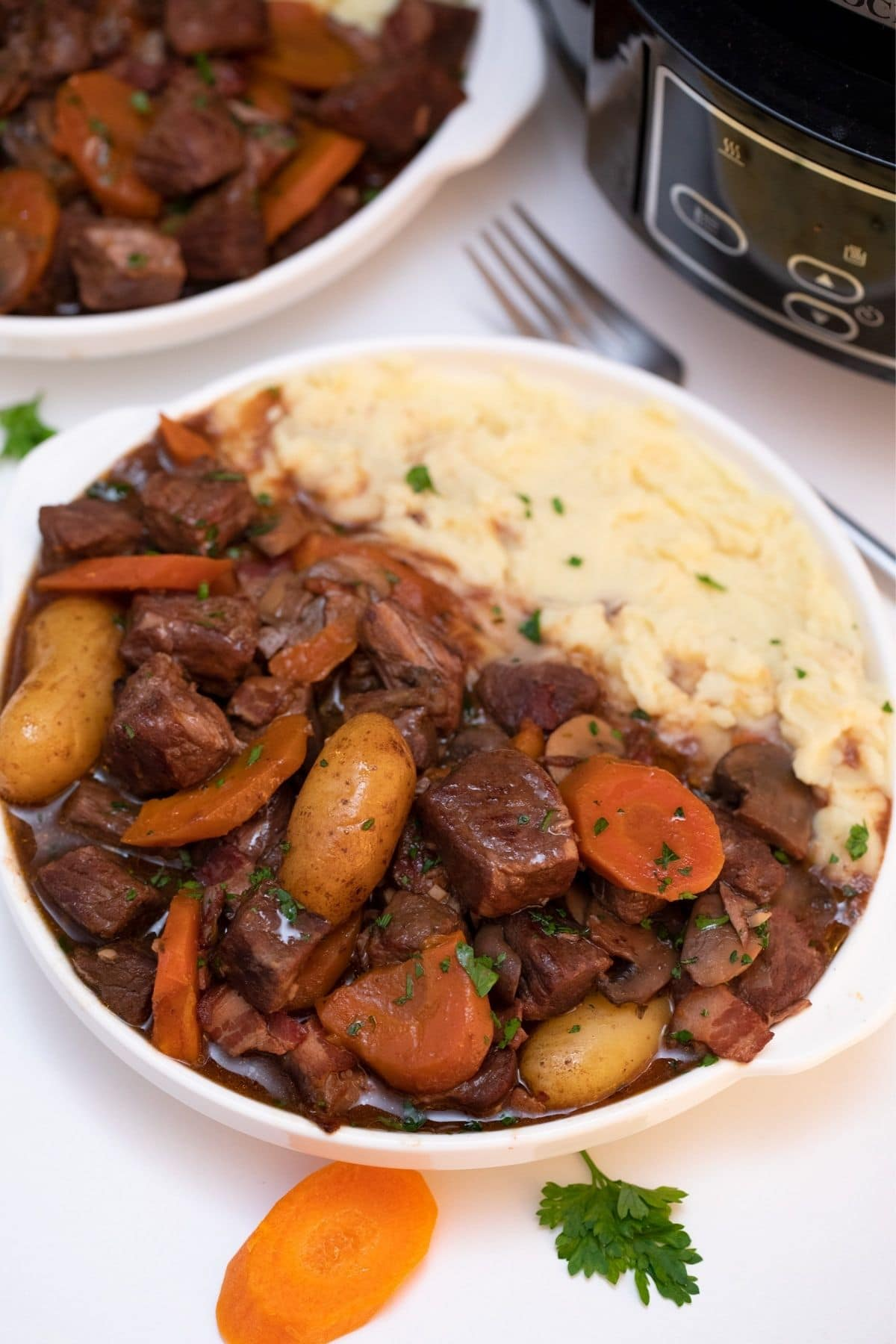 White bowl of mashed potatoes beef carrots and sauce on counter