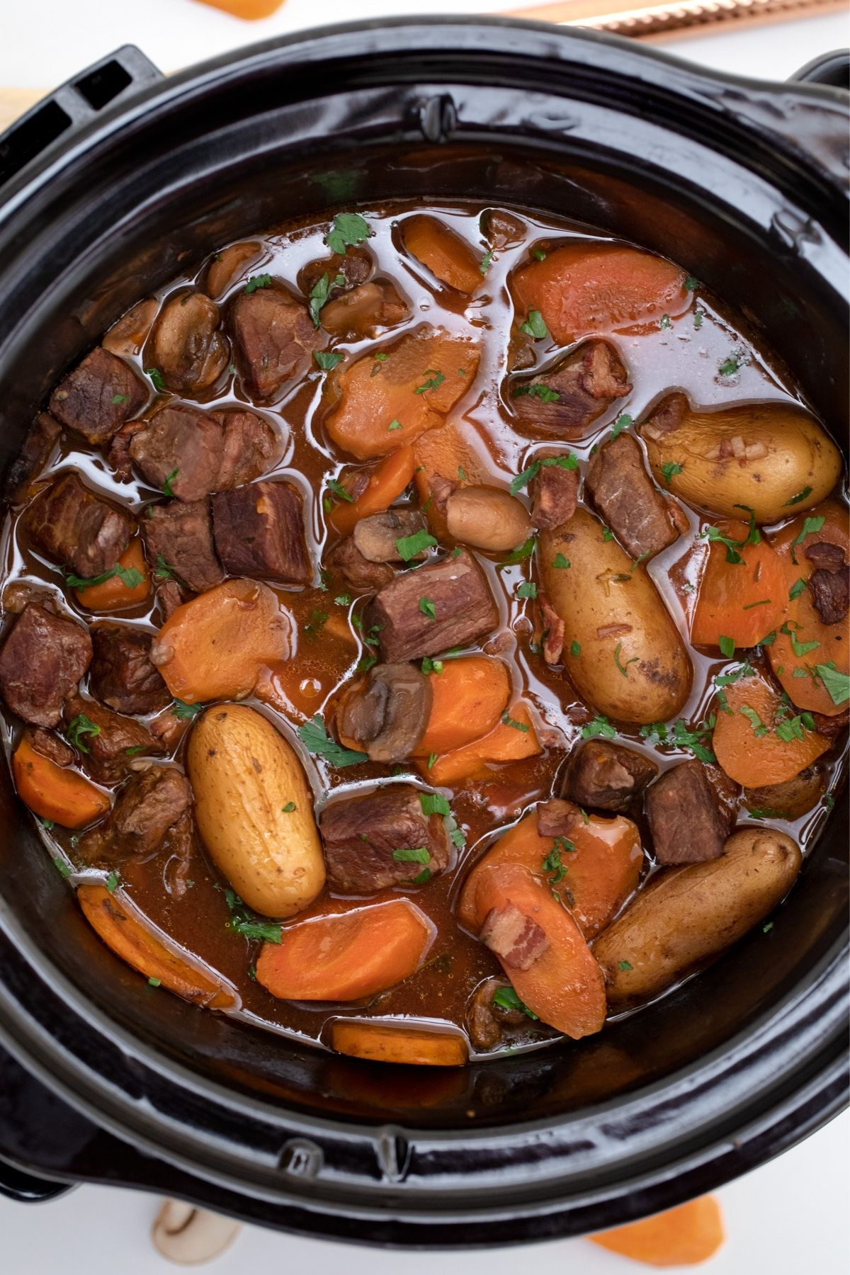 Round black crockpot filled with beef and vegetables in sauce