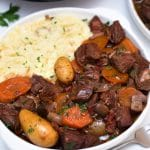 Large white bowl of potatoes and beef with carrots