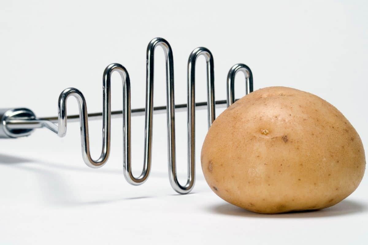 A piece of potato and a potato masher