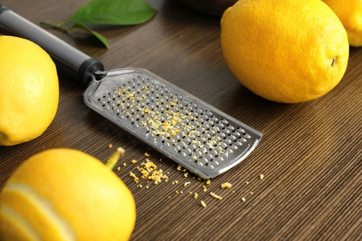 Fresh Lemon, Zest and Grater on Wooden Table