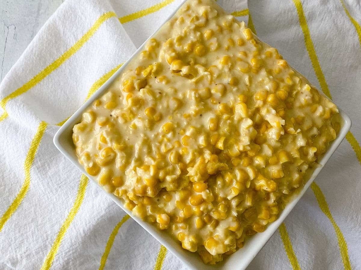 Square bowl of corn on yellow and white towel
