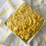 Creamed corn in square white bowl sitting on white and yellow napkin