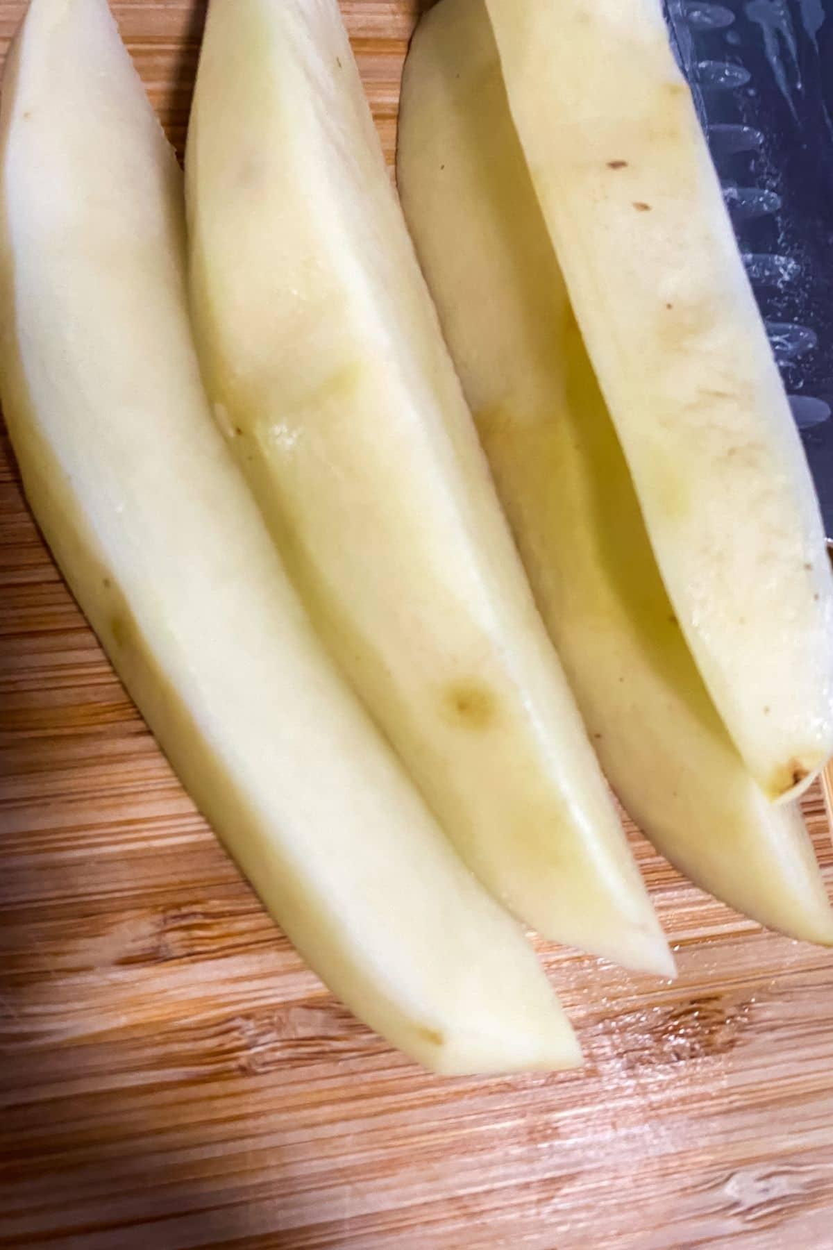 Peeled sliced potatoes on cutting board