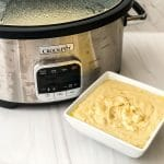 Silver crock Pot on white counter with white square bowl of creamy potatoes in front