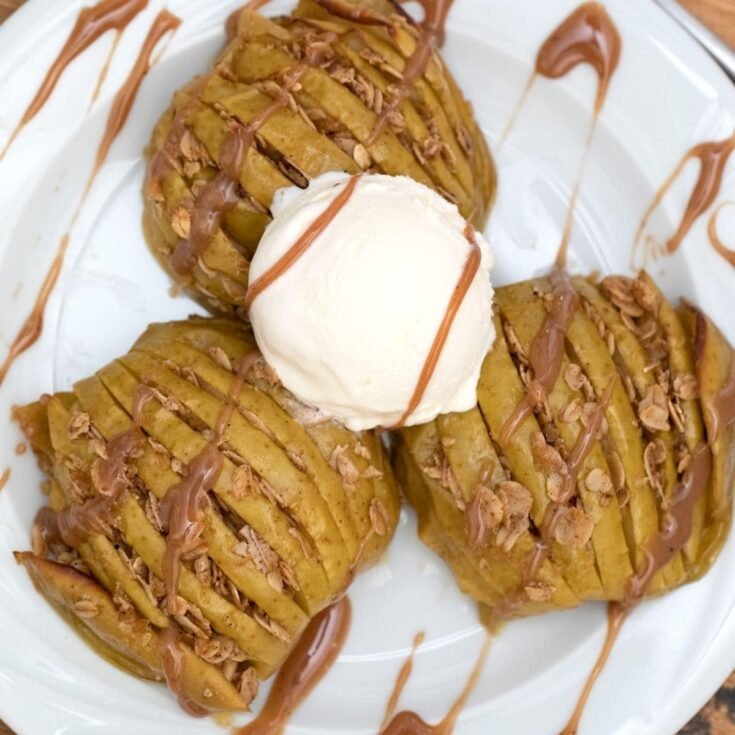 Three baked apple halves on white plate drizzled with caramel