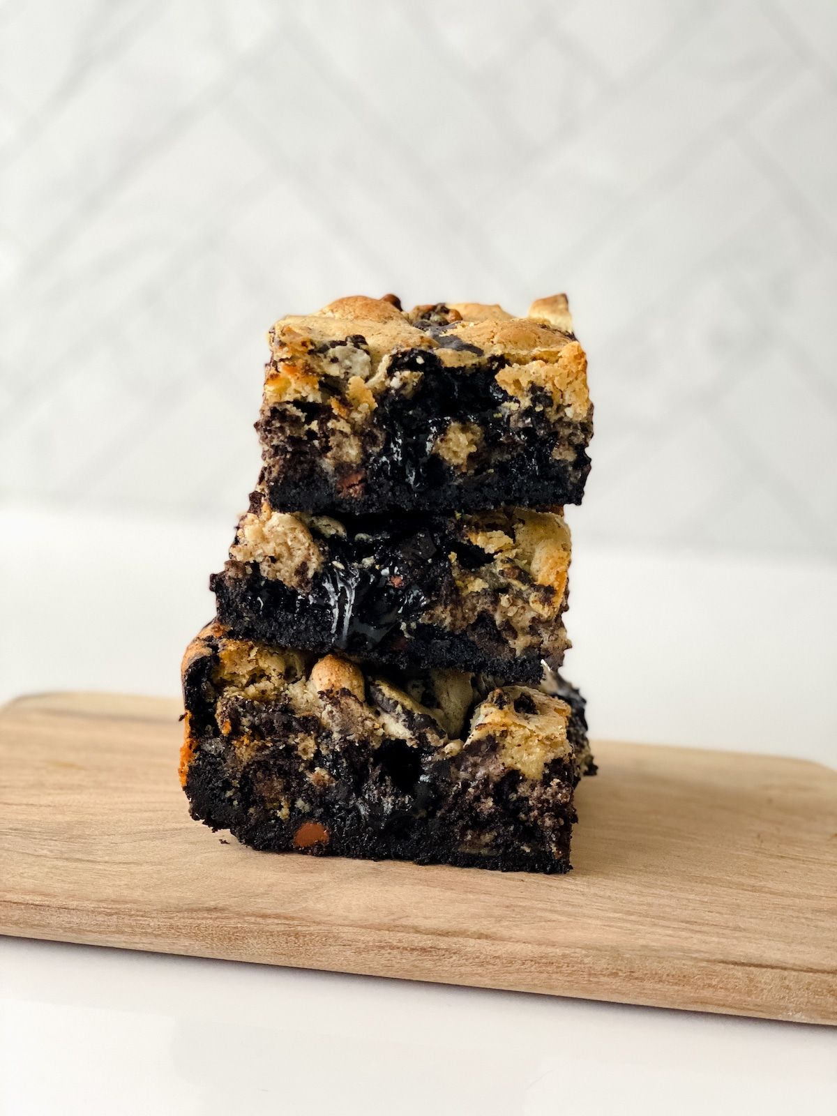 Stack of three brownies on wooden board on white counter