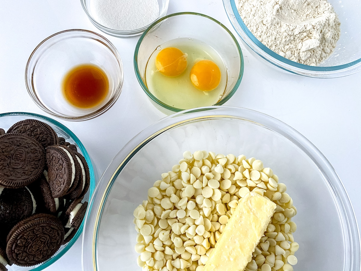 White chocolate and butter in large glass bowl next to cookie dough ingredients