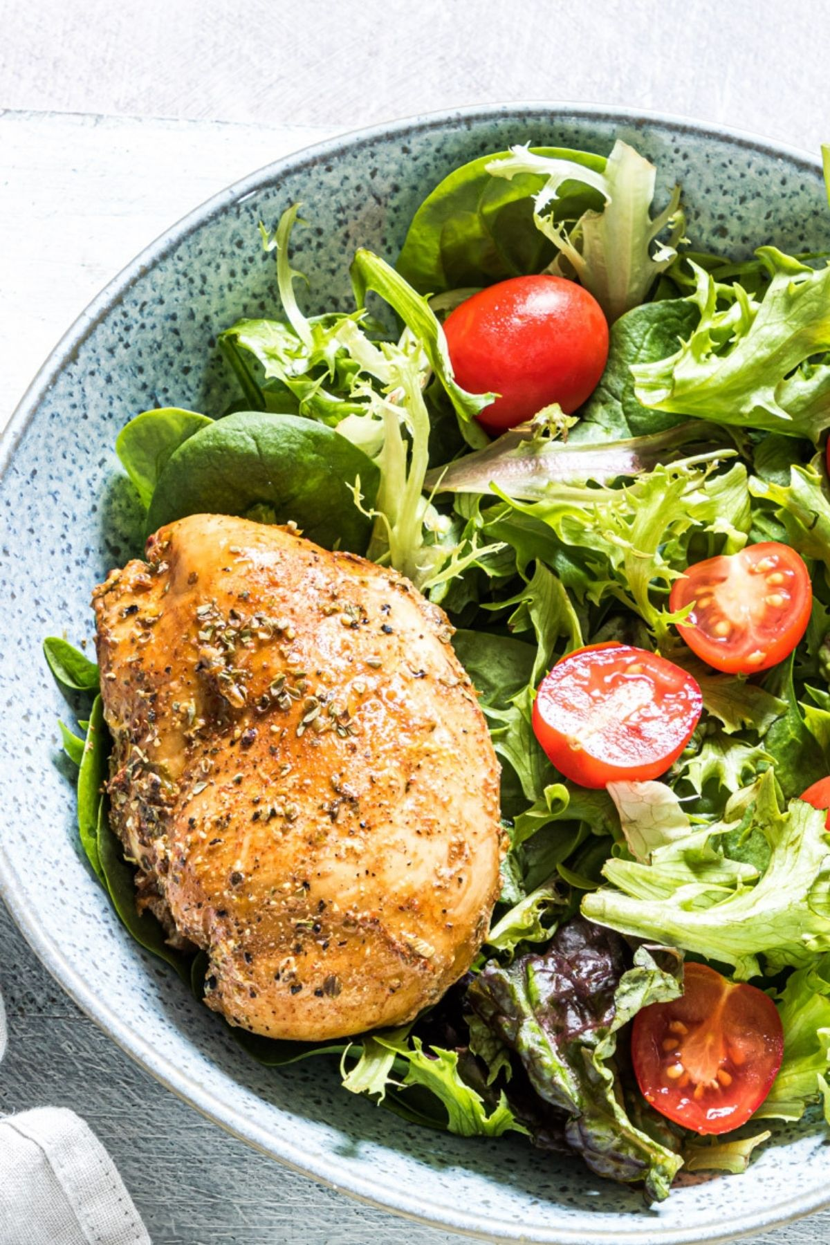 Blue bowl of salad with chicken breast