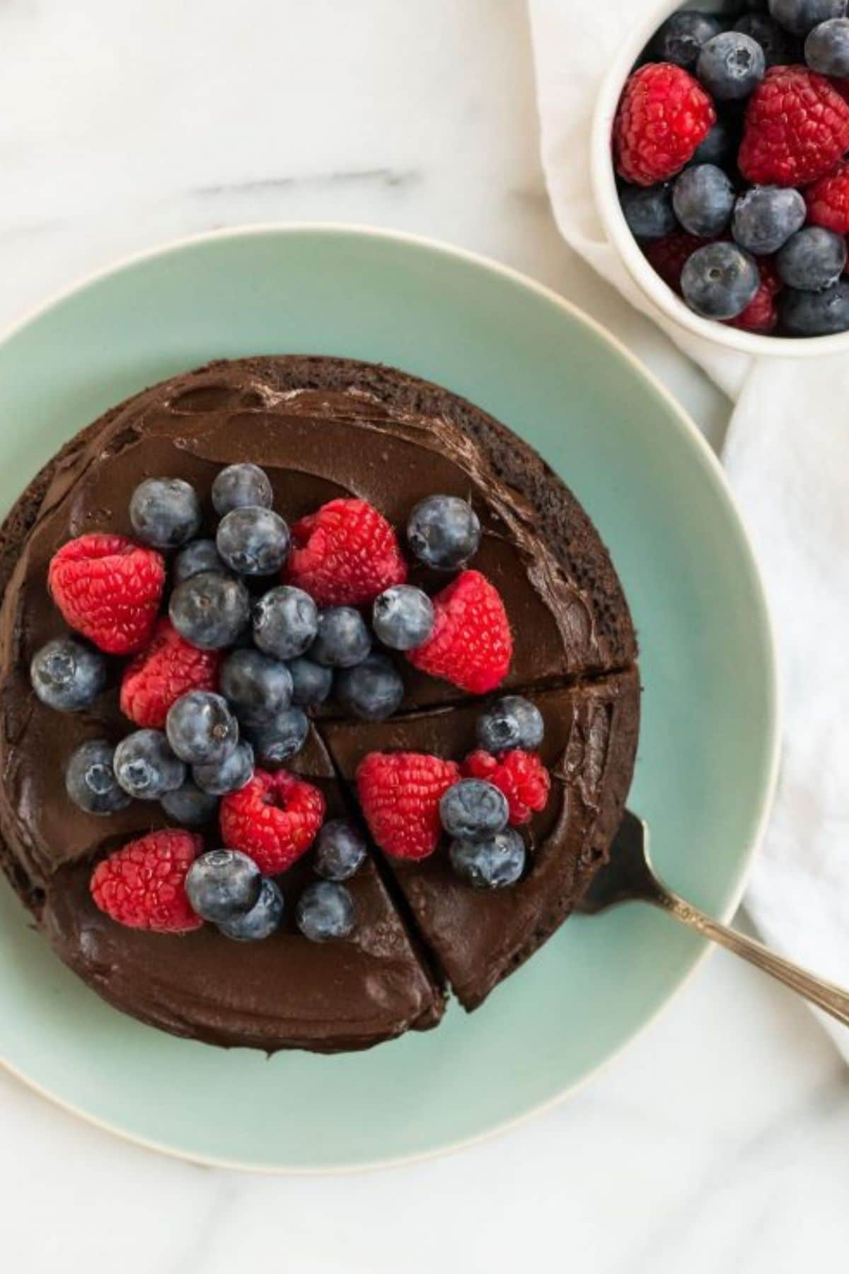 Chocolate cake on teal plate with blueberries and strawberries