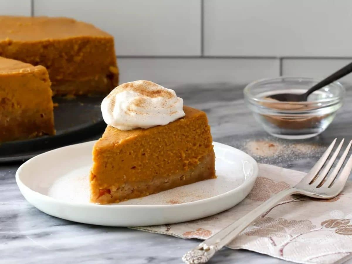 Slice of pumpkin pie on white plate