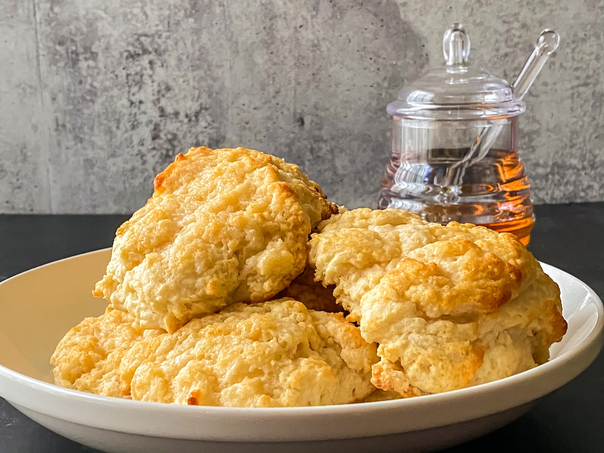 White plate of biscuits on black table with glass jar of honey in background