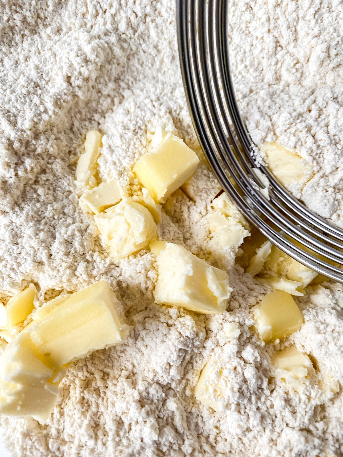 Flour in bowl with chunks of butter and pastry cutter