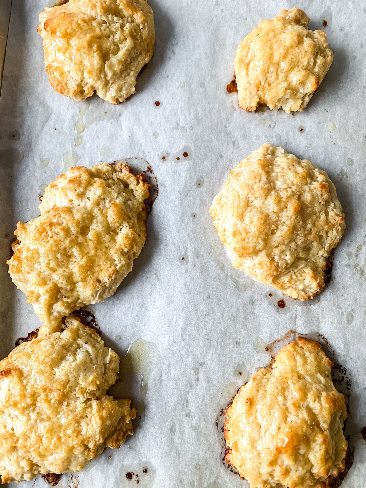 Baked biscuits on parchment lined baking sheet