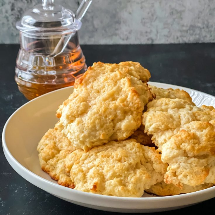 Biscuits on white plate on black table with jar of honey in background