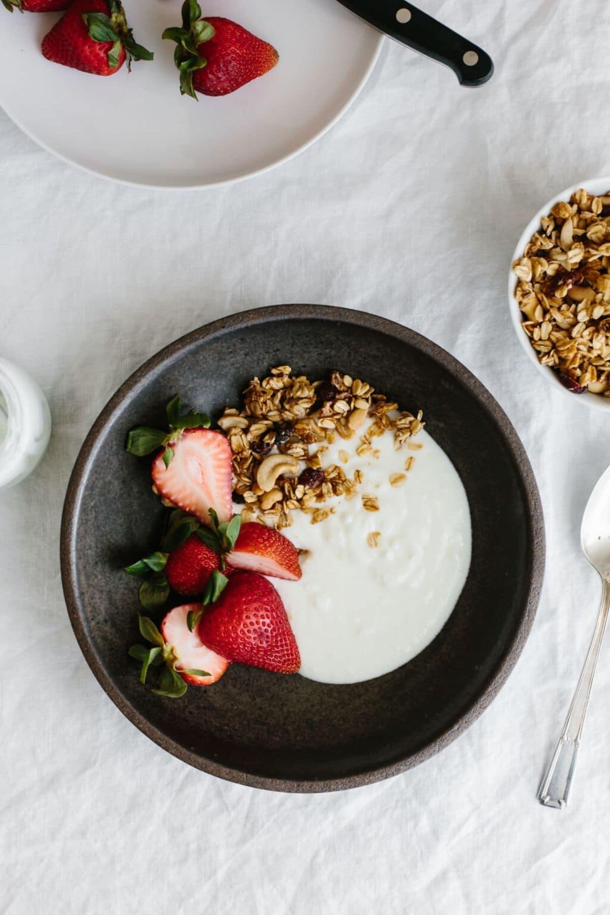 Black bowl of yogurt with sliced strawberries