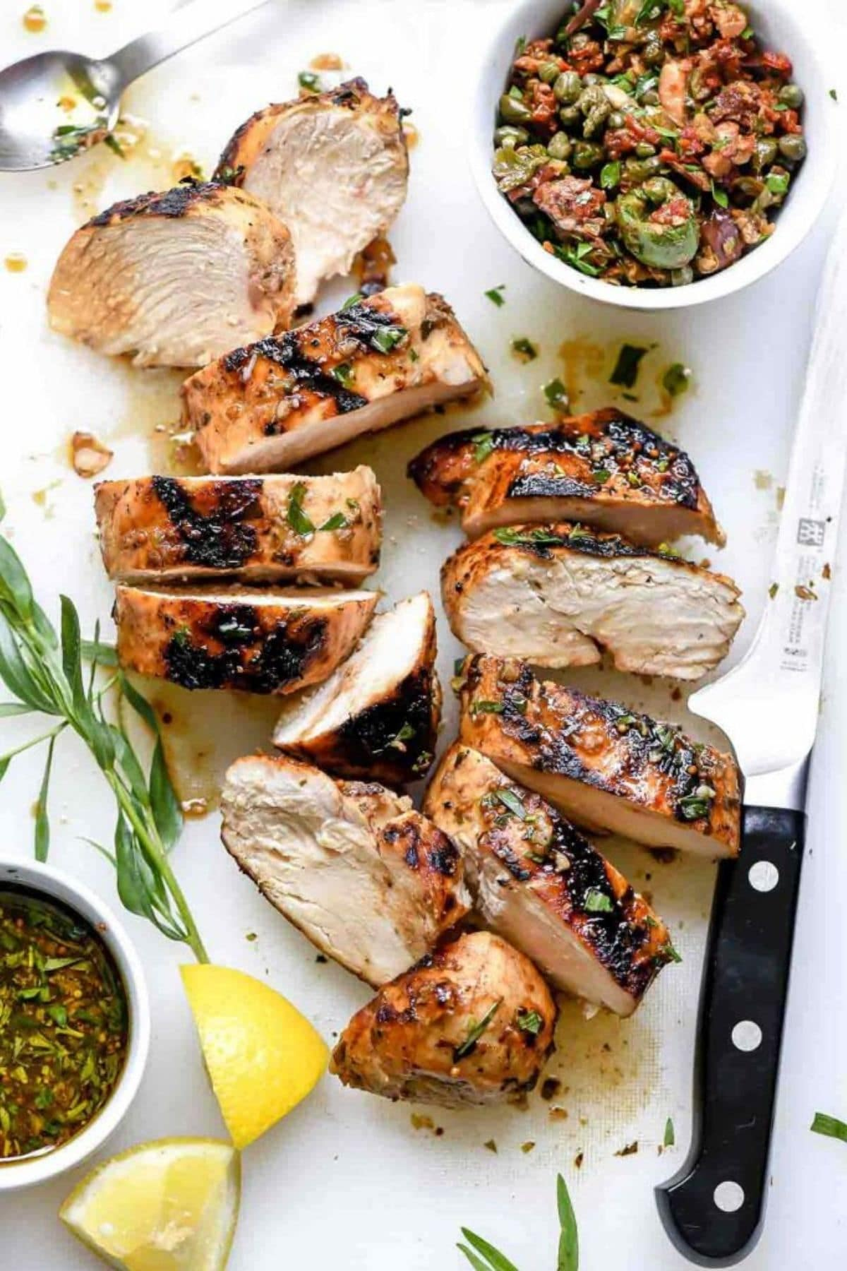 Sliced chicken breasts on white table next to olive tapanede