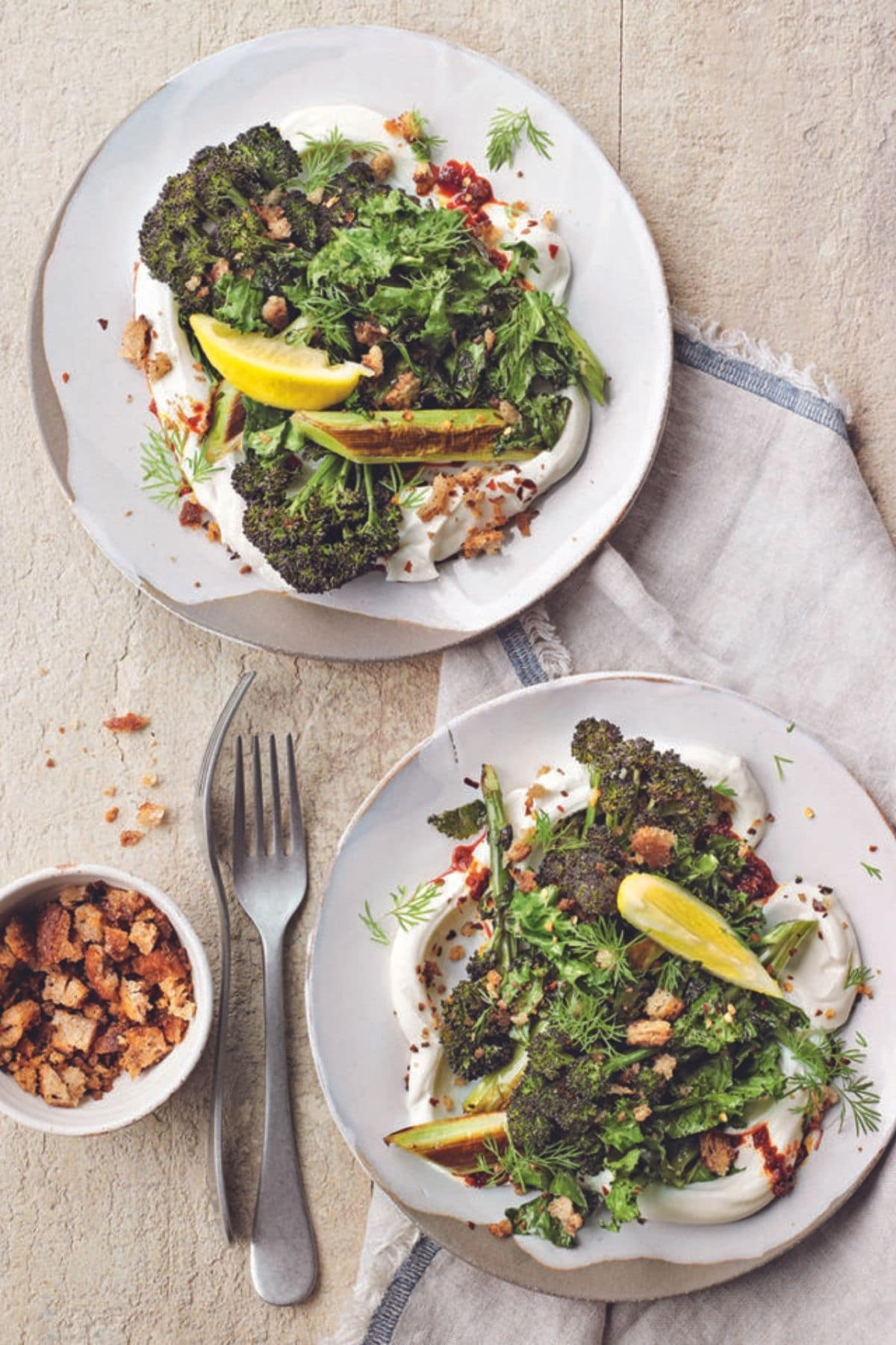 Greens with squash on white plates on brown table