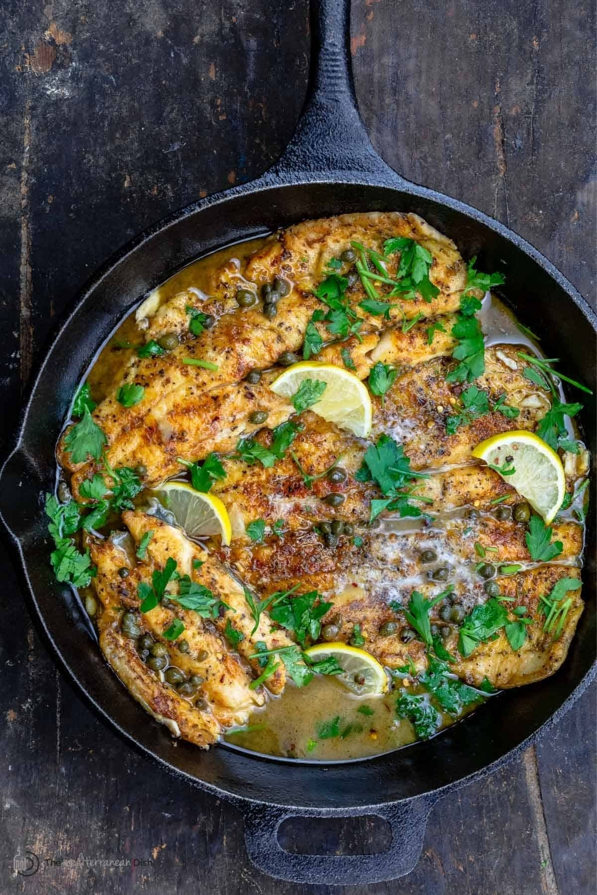 Fish piccata in cast iron skillet on wood table