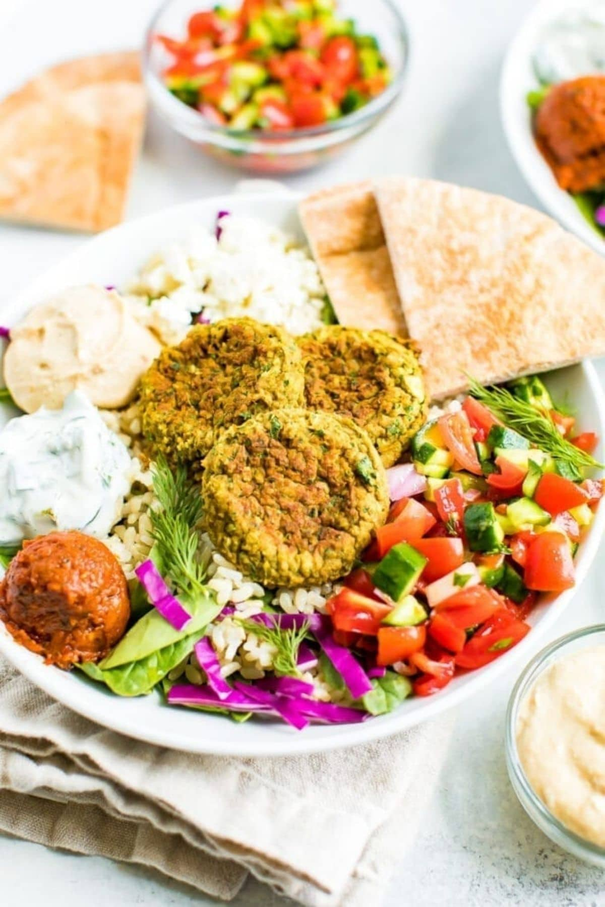 Bowl with greek salad falafel and pita on counter