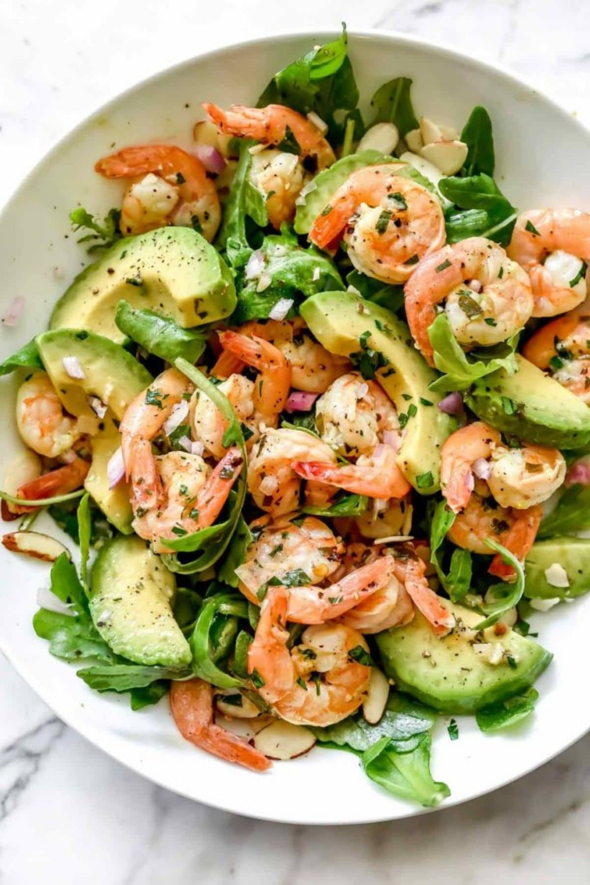 Shrimp and avocado on salad greens in white bowl on marble counter