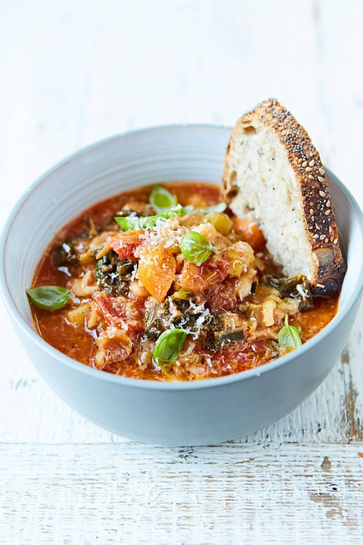 White bowl of minestrone soup topped with herbs and sliced bread