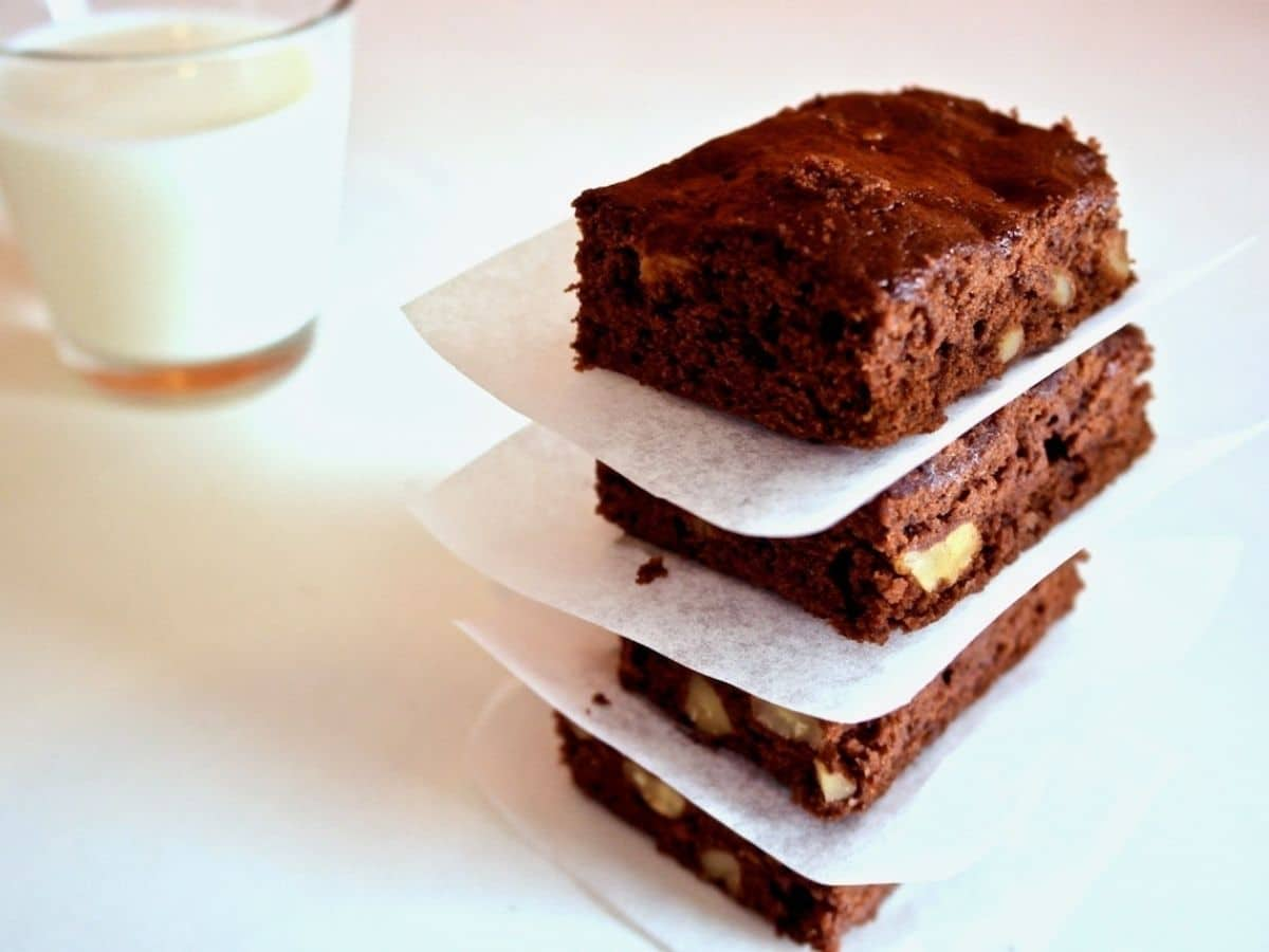 Stack of brownies separated by paper on white counter