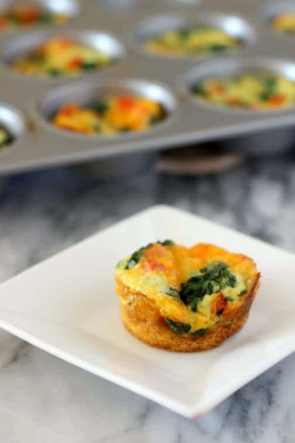 Single egg muffin on square white plate by muffin tin on table