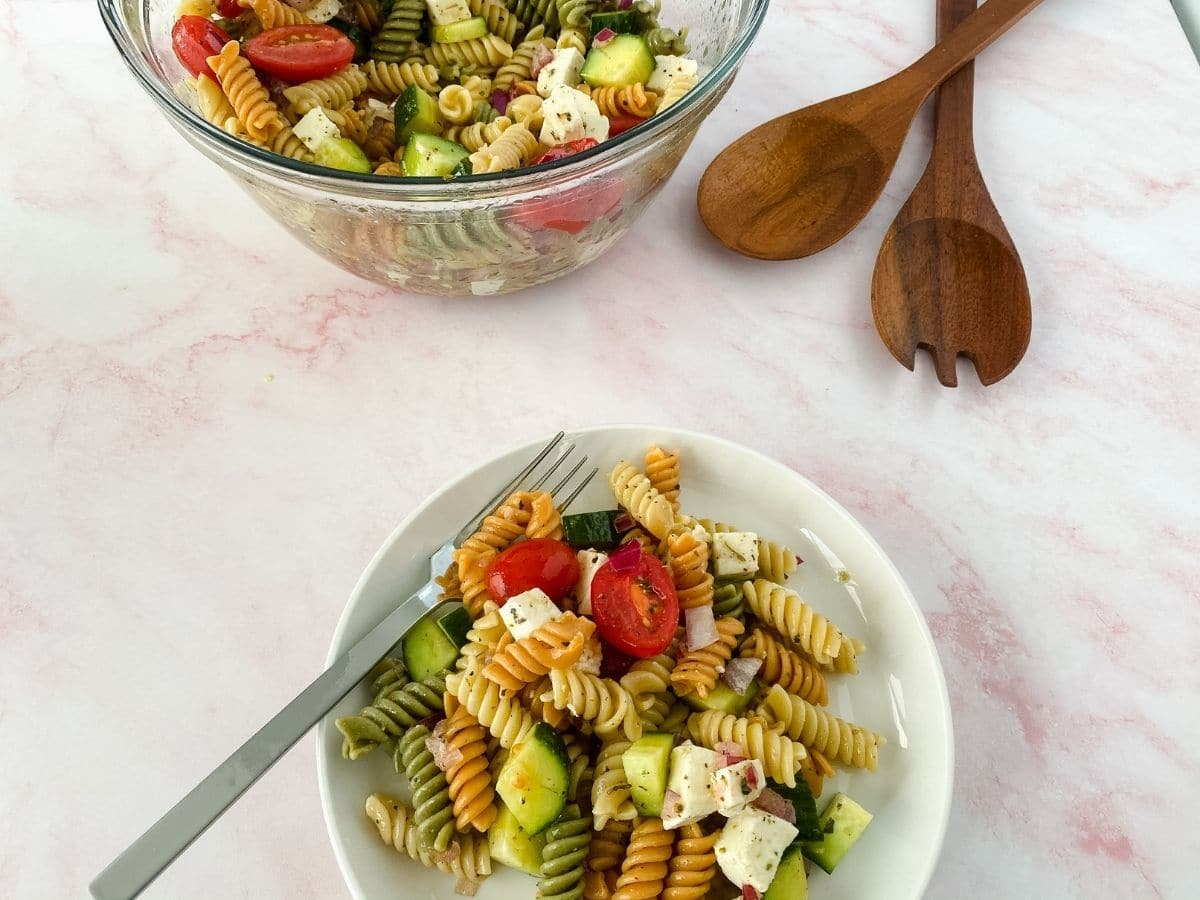 White bowl of pasta salad with fork in bowl next to wooden salad spoons