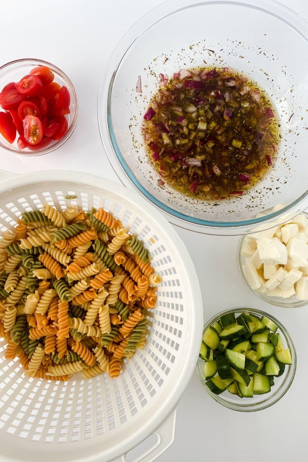Pasta in white colander next to glass bowl of vinaigrette