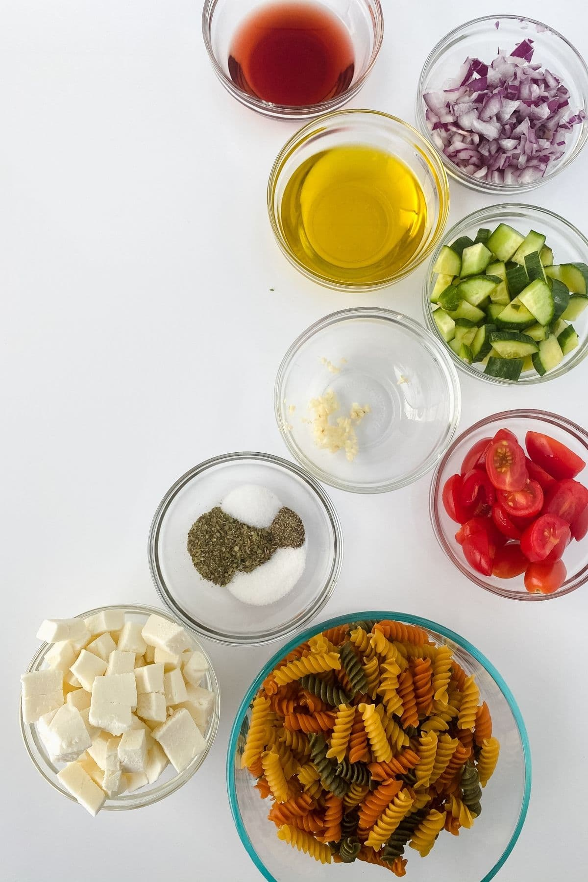 Ingredients for pasta salad in glass bowls on white table