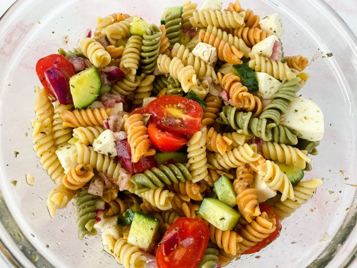 Glass bowl of pasta salad with cucumber feta and tomato