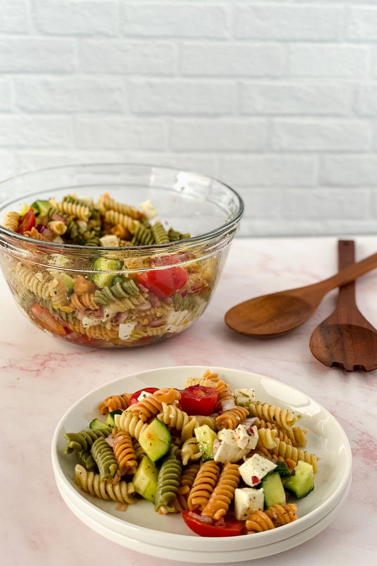 White shallow bowl of pasta salad on pink table in front of large glass bowl of salad