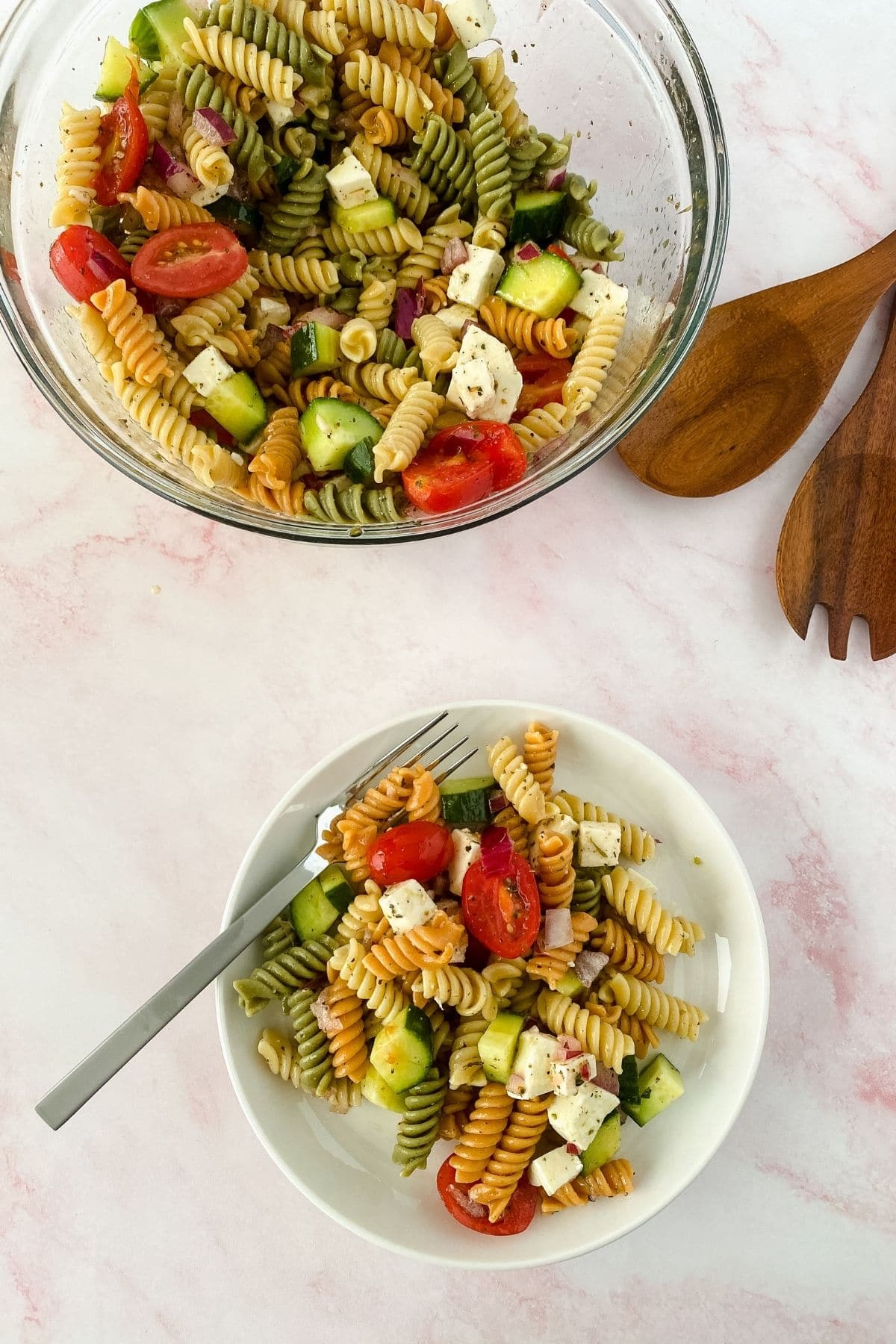 Image looking down on white bowl of pasta salad next to large glass bowl of salad