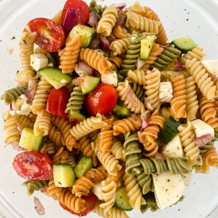 Glass bowl of rotini pasta with cheese cucumbers and tomato