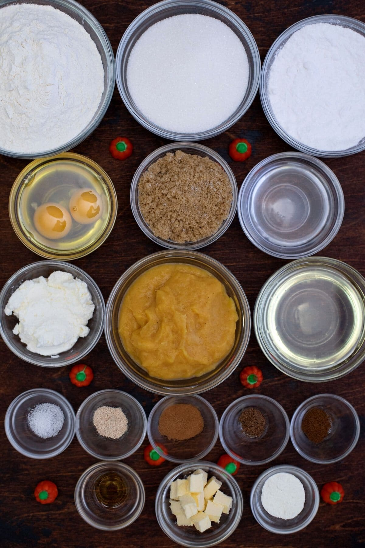Ingredients for pumpkin bread in glass bowls on dark wood table