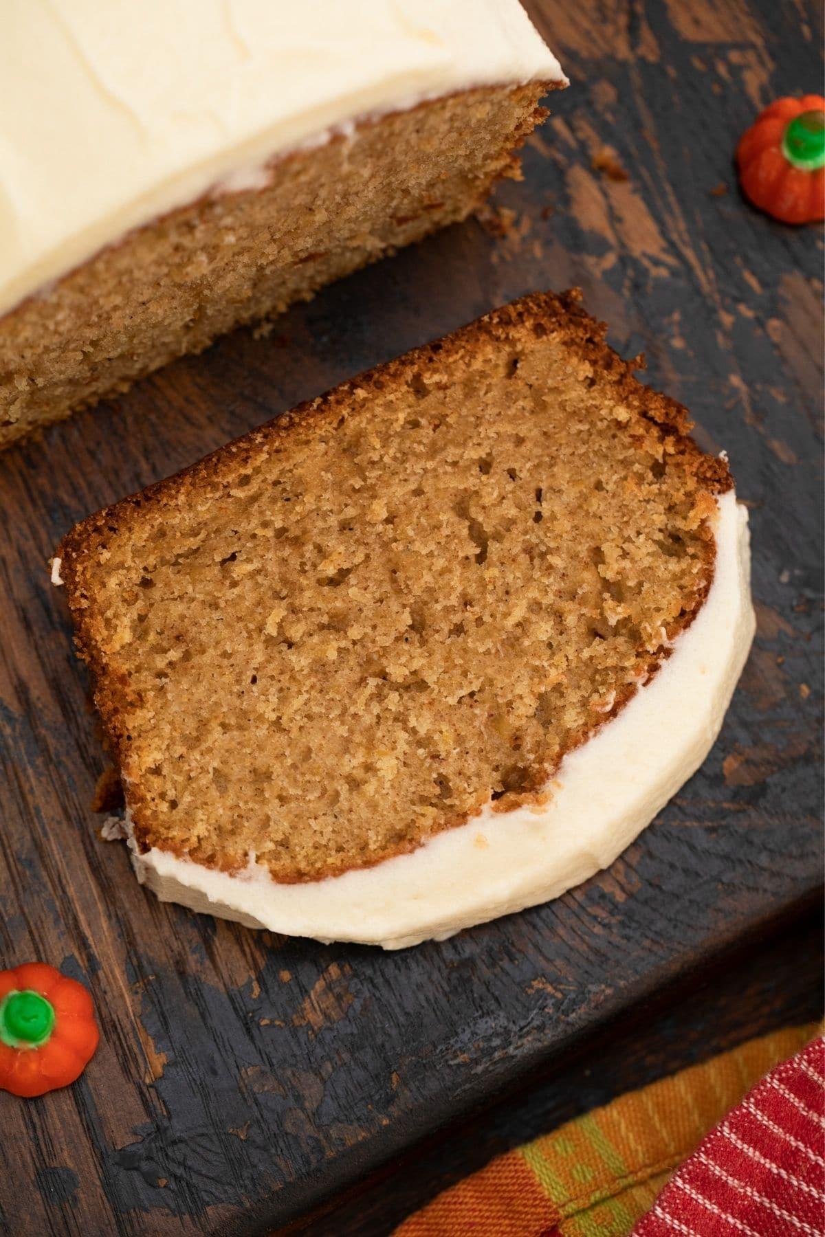 Single slice of pumpkin bread on dark wood board