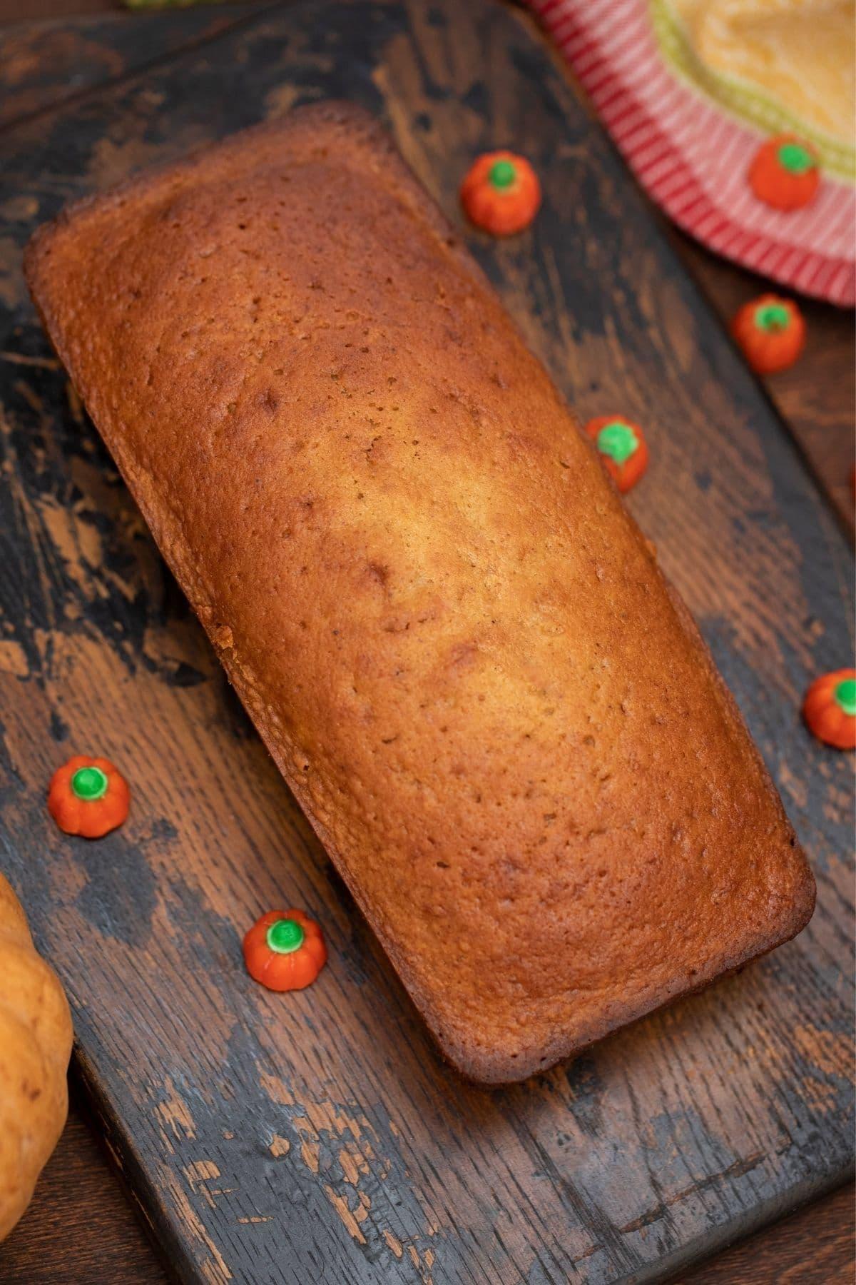 Whole loaf pumpkin bread on dark wood cutting board