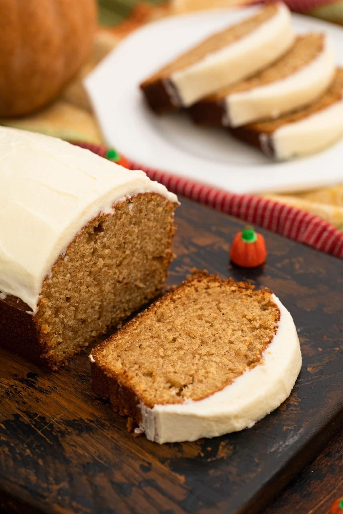 Half loaf of pumpkin bread on board next to saucer of sliced bread