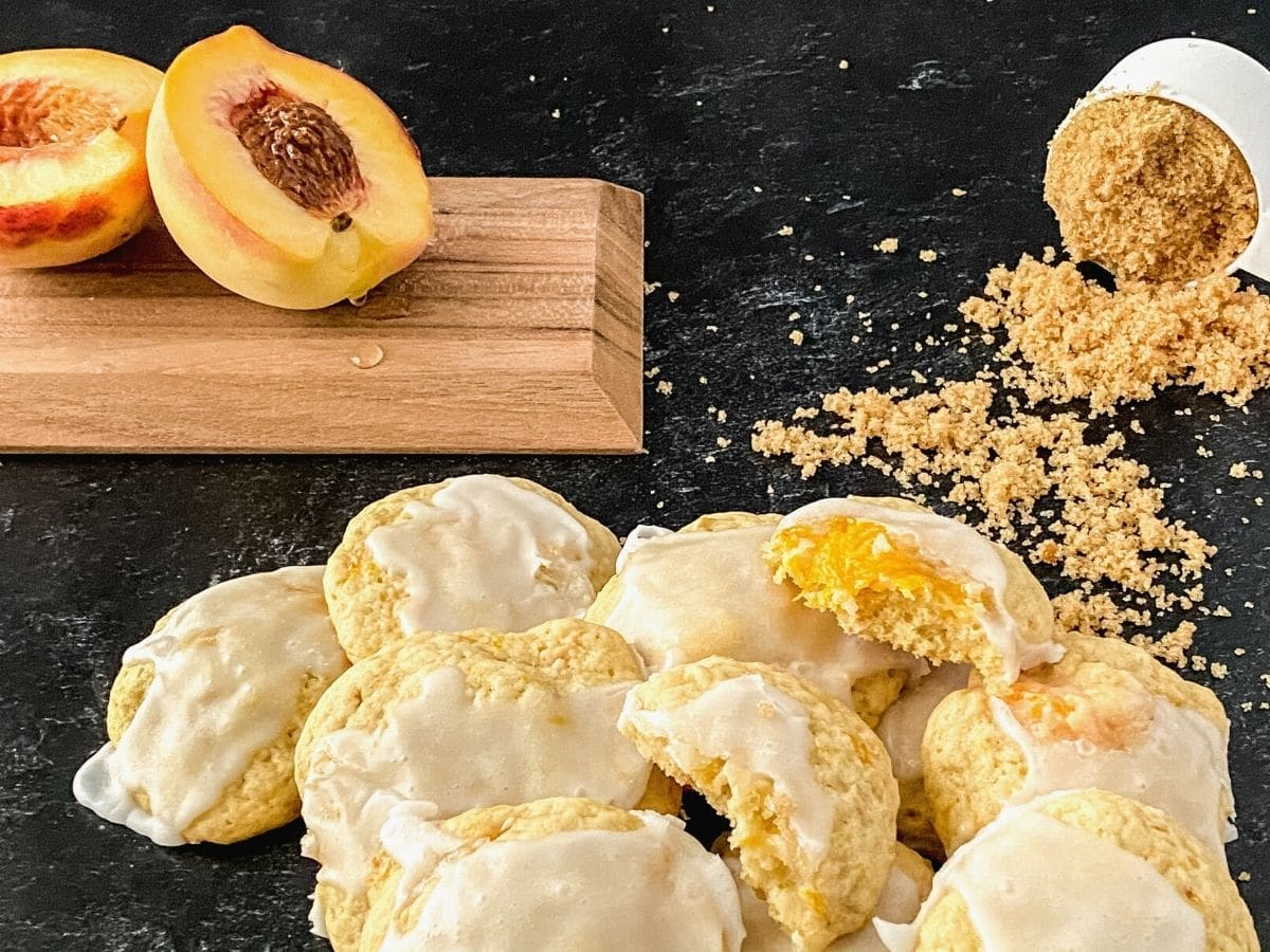 Peach cobbler cookies with glaze on black table with cutting board of peach in background