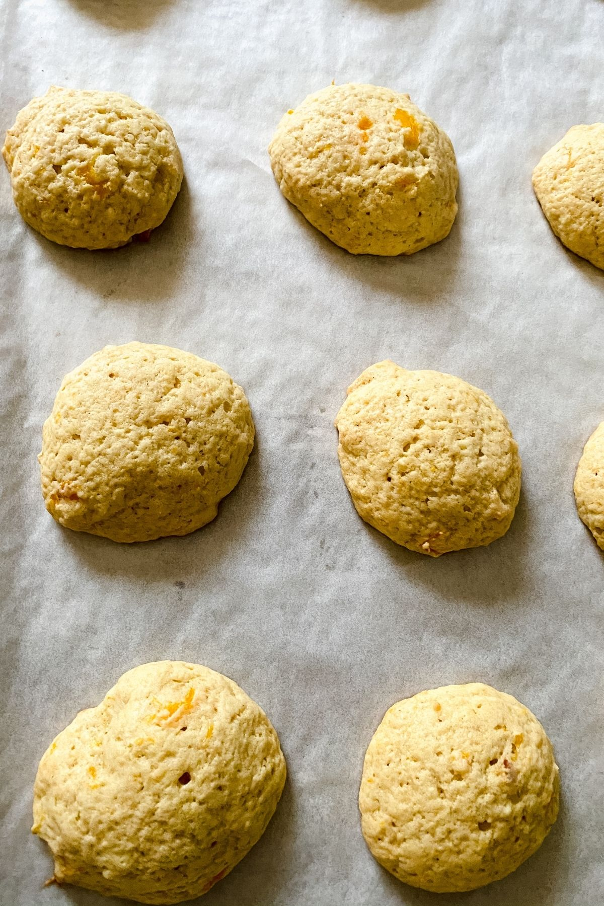 Light brown cookies on parchment lined baking sheet