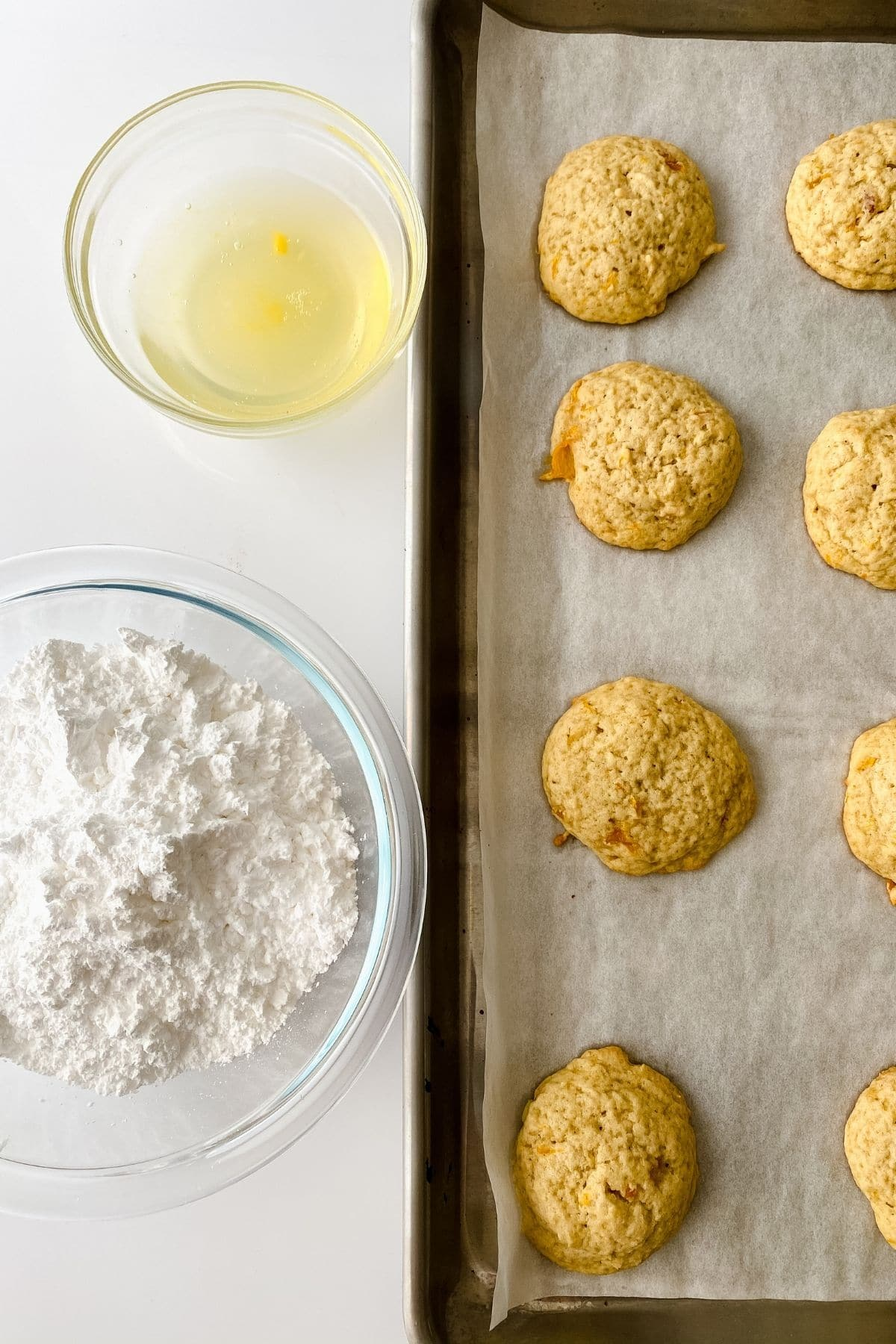 Baked cookies on baking sheet with bowl of powdered sugar on side